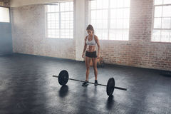 Strong crossfit female at gym with barbells. Full length portrait of muscular young woman standing at gym with barbells on floor. Strong crossfit female at gym Royalty Free Stock Image