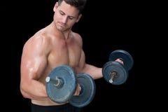 Strong crossfitter lifting heavy black dumbbells Stock Photo
