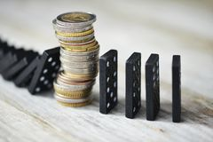 Strong currency or economy concept with pile of coins stopping the fall of black domino blocks royalty free stock photos