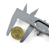 Strong Currency? Pound. Measuring a one pound coin with a caliper.  image on white background Stock Photography