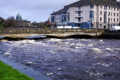 Strong current on river that about to go over bridge and riverbanks in Galway royalty free stock photos