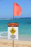Strong current warning sign. Strong current hazard sign and flag on an idyllic tropical beach warning swimmers of the dangers of a rip tide or undertow and royalty free stock image