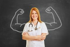Strong doctor with muscles of chalk. Strong female doctor stands in front of blackboard with chalky muscles Royalty Free Stock Images