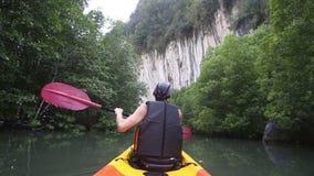 Strong elder man floats kayak to gray cliff stock video