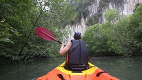 Strong elder man floats kayak to gray cliff stock video footage