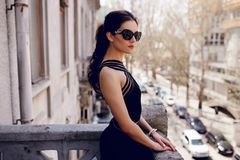 Strong, elegant woman in black sunglasses,sexy black dress, hair ponytail, looks with attitude at the balcony. royalty free stock images