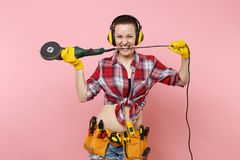 Strong energy handyman woman in yellow gloves, noise insulated headphones, kit tools belt full of instruments holding. Power saw isolated on pink background royalty free stock photo