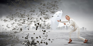 Strong enough to challenge it . Mixed media. Young blond businesswoman with white umbrella walking against the wind. Mixed media stock images