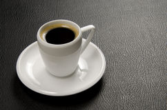 Strong Espresso shot. Espresso shot in a white cup against black leather Stock Photography