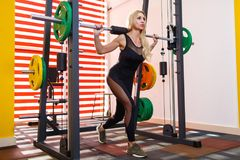 A strong blonde woman doing exercises with a barbell in the gym. A strong European blonde woman dressed in a black tight suit, doing exercises with a barbell in Royalty Free Stock Image