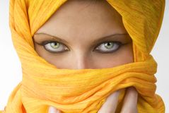 Strong eyes. Attactive and strong eyes behind an orange scarf used like a burka Royalty Free Stock Images