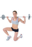 Strong female crossfitter lifting barbell behind head looking at camera Royalty Free Stock Images