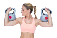 Strong female crossfitter lifting kettlebells Stock Photos