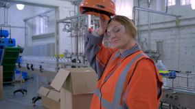 Strong female at factory, happy forceful woman into hard hat and working clothes carries big heavy box through plant. Enterprise stock video footage
