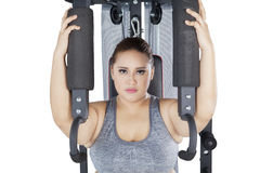 Strong female and shoulder press machine on studio. Picture of strong obese female looking at the camera while workout on a shoulder press machine in the studio stock image