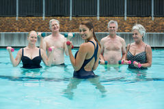 Strong female trainer with senior swimmers in swimming pool Royalty Free Stock Photo