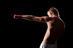 Strong fighter boxing. Over black background stock photo