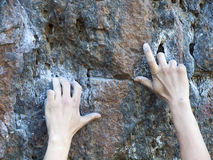 Strong fingers climb the mountain. Stock Photo