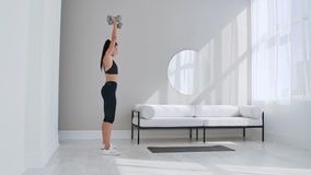 Strong and fit beautiful girl in an athletic top is doing squat exercises in her bright and spacious living room with. Minimalistic interior stock video