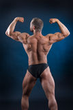 Strong fit man demonstrating his powerful back. Handsome bodybuilder demonstrating his strong body and powerful back Royalty Free Stock Image