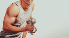 Strong fit man exercising with dumbbells. Royalty Free Stock Photos