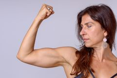 Strong fit mature woman flexing her arm muscles. Strong fit mature woman clenching her fist and flexing her arm muscles showing off her toned biceps over a grey Stock Photos