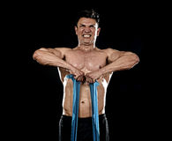Strong fit sport man training hard with elastic rubber band working muscles sweating Royalty Free Stock Photo