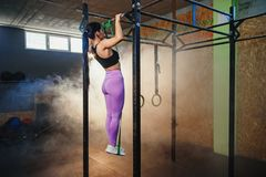 Strong fit woman doing pull up on horizontal bar. Back view of strong fit woman in sportswear doing pull up on horizontal bar during training in dark gym full stock images