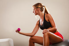 Strong fit woman exercising with dumbbell. Bodybuilding. Strong fit woman exercising with dumbbell. Muscular blonde girl lifting weights Stock Image
