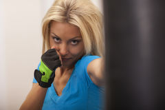 Strong fit woman exercising in a gym with punching bag. Slim blond girl in blue t-shirt and black pants. Strong fit woman exercising in a gym with punching bag Stock Photos
