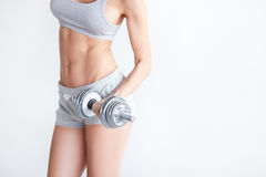 Strong fit woman exercising with iron dumbbell Stock Photos