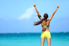 Strong fitness athlete arms up in success on summer beach. After cardio training workout. Female runner woman running winning reaching goal achievement during royalty free stock photos