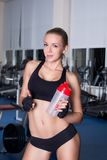 Strong fitness girl with cocktail bottle after Stock Images