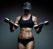 Strong fitness woman bodybuilder. With tanned body pumps up the muscles lifting dumbbells stock photos