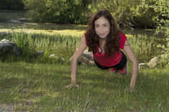 Strong fitness woman doing push-ups in nature Stock Photo