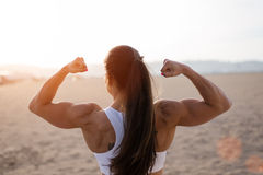 Strong fitness woman flexing biceps on sunset Royalty Free Stock Photo
