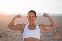Strong fitness woman flexing biceps on sunset. Young fitness woman flexing big strong biceps muscles towards the sun at urban beach. Cheerful female bodybuilder royalty free stock photo