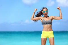 Strong fitness woman having fun showing off muscular arms. Strong fitness funny woman in neon blue wayfarer sunglasses on beach showing off muscular arms flexing stock photography