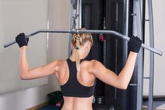 Strong fitness woman perfoming back exercise in. Gym. Power training. Workout Royalty Free Stock Images