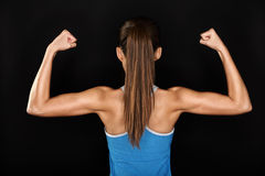 Strong fitness woman showing back biceps muscles. Strong fitness woman showing back and biceps muscles strength. Fit girl fitness model isolated on black Royalty Free Stock Image