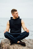 Strong fitness yoga man in lotus pose on the rock beach near the ocean. Harmonic concept. Stock Image