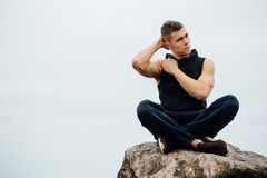 Strong fitness yoga man in lotus pose on the rock beach near the ocean. Harmonic concept. Stock Photos