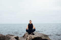 Strong fitness yoga man in lotus pose on the rock beach near the ocean. Harmonic concept. Strong fitness yoga man in lotus pose on the rock beach near the ocean Royalty Free Stock Photography