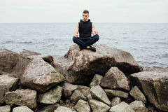 Strong fitness yoga man in lotus pose on the rock beach near the ocean. Harmonic concept. Strong fitness yoga man in lotus pose on the rock beach near the ocean Royalty Free Stock Images