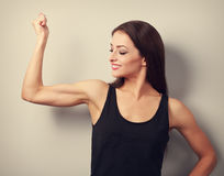 Strong fitness young woman showing muscle bicep with happy smili Stock Images