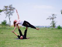Morning yoga in the city green park. A beautiful couple holds a yoga class. Strong and flexible young couple doing acrobatic workout. Two women in park Royalty Free Stock Image