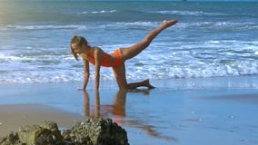 Strong Foamy Waves Wash Girl Body Doing Exercise on Beach stock video
