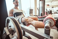 Strong focused man is doing legs exercises on training apparatus royalty free stock images