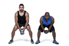 Strong friends lifting kettlebells together Royalty Free Stock Photography