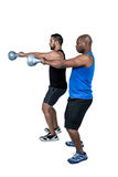 Strong friends lifting kettlebells together Royalty Free Stock Image